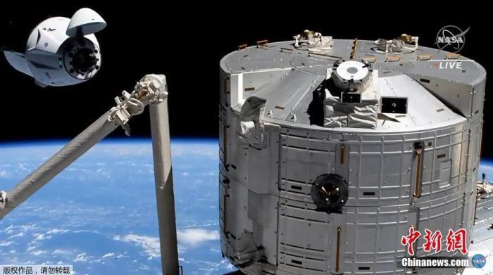 """资料图:搭乘美国太空探索技术公司(SpaceX)载人""""龙""""飞船的4名宇航员抵达国际空间站。这是有史以来首次使用回收的载人飞船完成航天飞行任务。图为""""龙""""飞船靠近国际空间站。"""