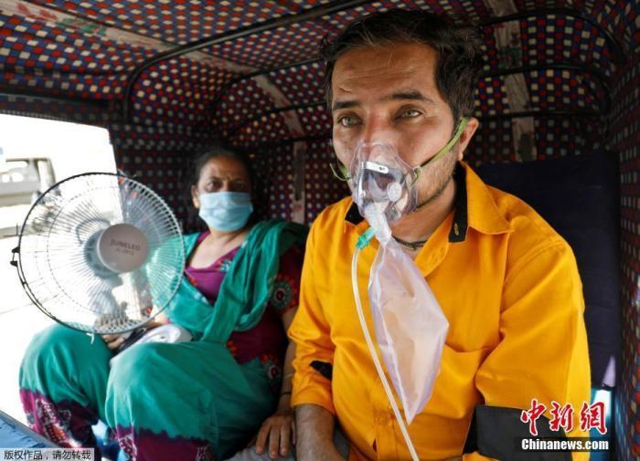 當地時間4月25日,一名患者和他的妻子在三輪車內等待進入醫院接受治療。