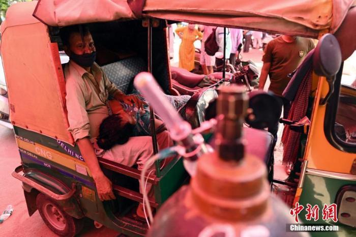 当地时间4月26日,印度加兹阿巴德路边的人力三轮车内,一名患者在他人的帮助下吸氧。