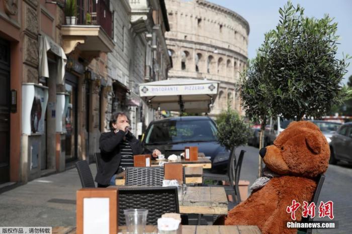 图为罗马斗兽场四周的酒吧,顾主在露台上喝酒。