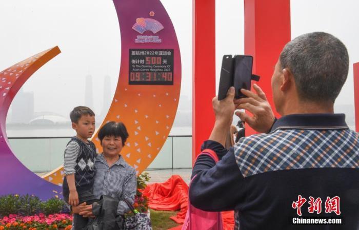 4月28日,浙江杭州,市民在杭州亚运会倒计时500天计时装置前拍照留影。当日,杭州2022年第19届亚运会进入开幕倒计时500天,首批倒计时装置亮相杭州。 中新社记者 王刚 摄