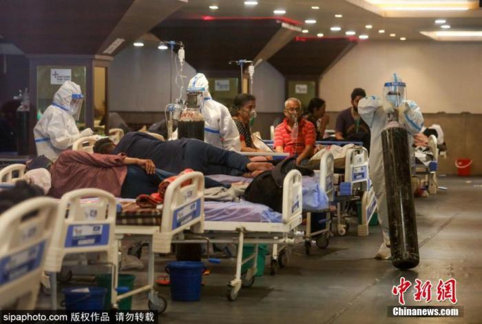 4月27日,印度通報新增逾32萬新冠確診病例,連續第6天超過30萬例,累計確診升至近1800萬,死亡人數逼近20萬。連續激增的確診病例,導致印度多地醫療系統癱瘓,許多患者只能在臨時搭建的場所接受治療。圖為醫護人員在運送氧氣罐。
