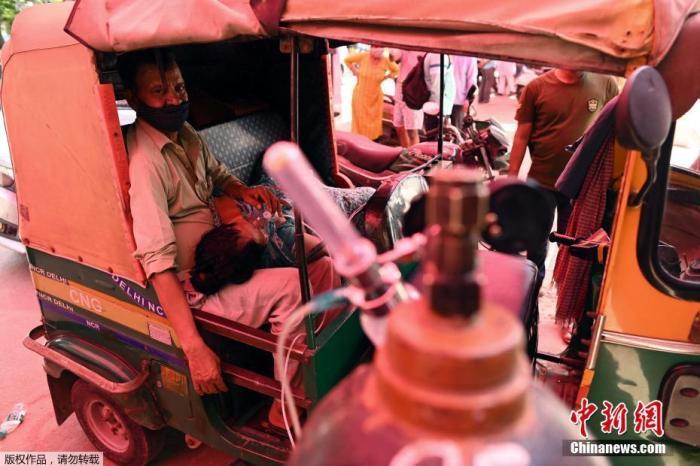 當地時間4月26日,印度加茲阿巴德路邊的人力三輪車內,一名患者在他人的幫助下吸氧。