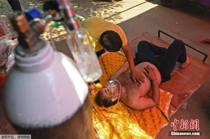 当地时间4月26日,印度加兹阿巴德,一名新冠患者在路边搭建的帐篷内吸氧。近日,印度新冠患者确诊病例连续出现增长高峰,几天内新增病例超百万,印度多地医院出现床位短缺、氧气供应困难等现象,许多病人只能在户外等候接受治疗。