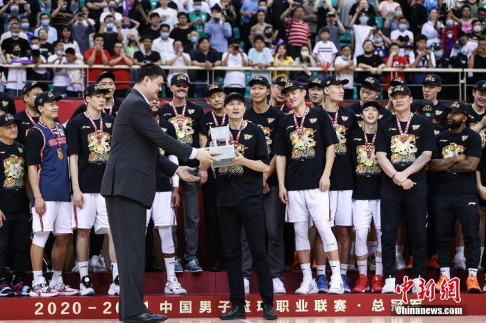 2020-2021赛季CBA总决赛于5月1日晚落下帷幕。最终广东男篮经过加时以110:103击败辽宁男篮,蝉联CBA总冠军,这也是其队史第十一冠。图为姚明为冠军球队颁奖。图片来源:视觉中国