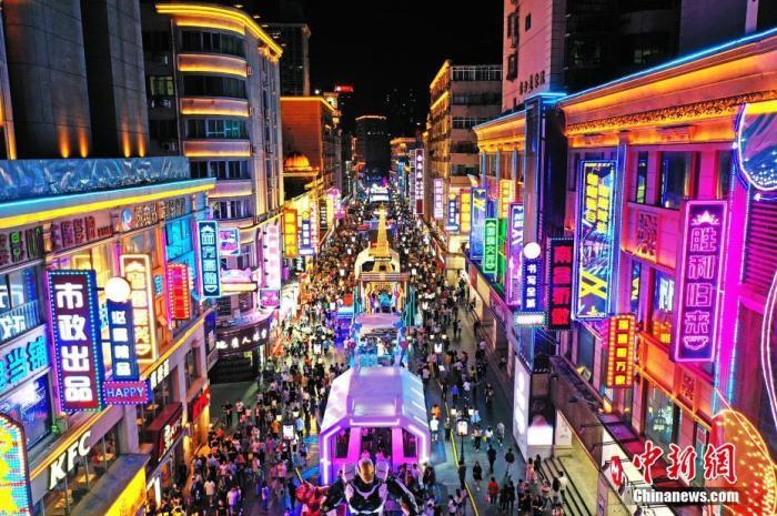 """5月2日晚,江西南昌,民众在胜利路步行街休闲购物。为恢复百年老街的往日繁华,当地开展胜利路步行街""""胜利归来"""" 主题活动,打造潮玩、消费于一体的活动街区,""""五一""""假期吸引民众,形成新的节日经济、夜间经济和文化经济。(无人机照片) <a target='_blank' href='http://www.chinanews.com/'>中新社</a>记者 刘占昆 摄"""
