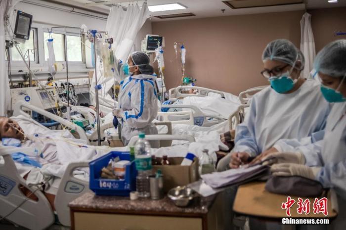資料圖:2021年5月6日,印度新德里,醫務人員在圣家醫院的ICU病房照料新冠肺炎患者。 圖片來源:視覺中國