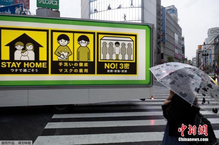 图为一辆装有新冠肺炎病毒预防措施屏幕的卡车驶过东京涉谷路口。