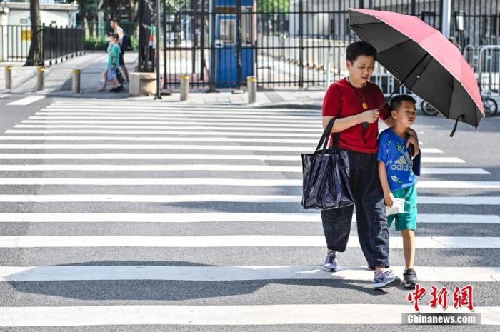 5月9日,广东省广州市,行人撑伞遮挡阳光。当日,广州市气象台发布了高温黄色预警信号,这是今年广州市气象台发布的首个高温预警信号。 <a target='_blank' href='http://www.chinanews.com/'>中新社</a>记者 陈骥旻 摄