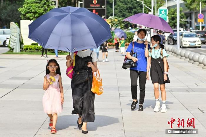 资料图:行人撑伞遮挡阳光。中新社记者 陈骥旻 摄
