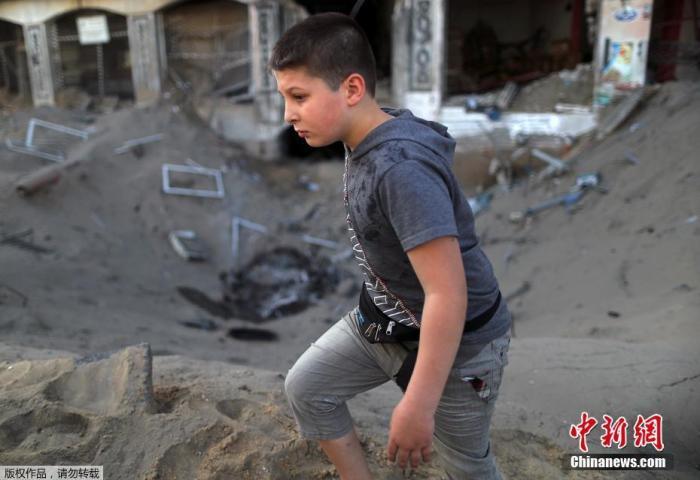 当地时间5月12日,巴以冲突期间,一名巴勒斯坦男孩儿在满是尘土的街头行走。