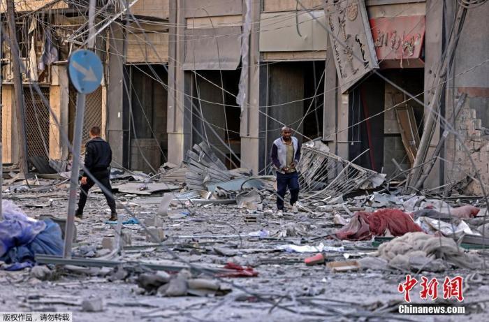 当地时间5月12日,巴以冲突期间,人们在受损严重的街头行走。