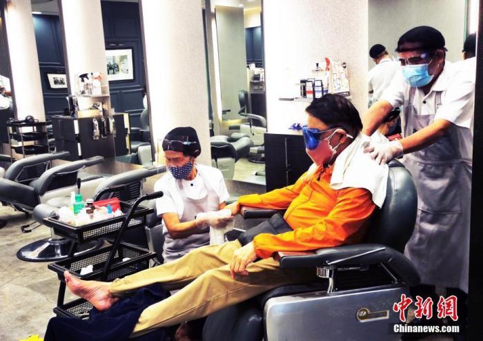 5月15日,马尼拉CBD马卡蒂一美发沙龙,服务员为顾客进行个人护理服务。 中新社记者 关向东 摄