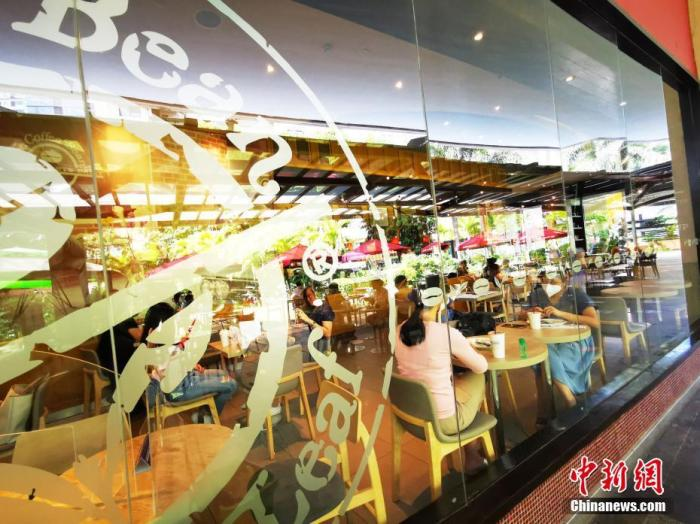 """5月15日,马尼拉CBD马卡蒂一咖啡厅,顾客在堂食。当天,菲律宾首都大马尼拉地区及邻近4省布拉干、甲米地、拉古那、黎刹(NCR Plus),防疫隔离分类降级为""""一般社区隔离(GCQ)""""。按照规定,允许室内和室外用餐服务,室内用餐人数限制在餐厅座位的20%,室外限制在50%。  中新社记者 关向东 摄"""