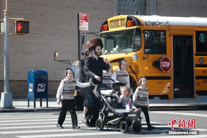 资料图:当地时间5月17日,民众从美国纽约市犹太社区的一所学校外经过。 中新社记者 廖攀 摄