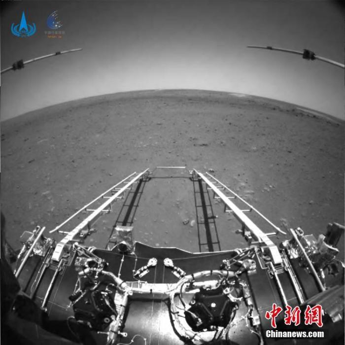 """中国国家航天局19日发布天问一号任务探测器着陆过程两器分离和着陆后""""祝融号""""火星车拍摄的影像。图像中,着陆平台和""""祝融号""""火星车的驶离坡道、太阳翼、天线等机构展开正常到位。  图为前避障相机图像。(图中着陆平台、坡道可见)  图片由火星车前避障相机拍摄,正对火星车前进方向。图中可见坡道机构展开正常;图像上部的两个伸杆为已经展开到位的次表层雷达;前进方向地形清晰。为获知火星车前进方向更大范围的地形信息,避障相机采用大广角镜头,在广角镜头畸变的影响下,远处地平线形成一条弧线。  国家航天局 供图"""