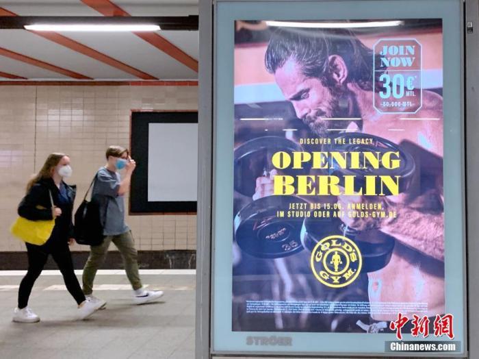"""图为柏林地铁站内的行人经过一处写有""""重启柏林""""的健身房广告。 中新社记者 彭大伟 摄"""