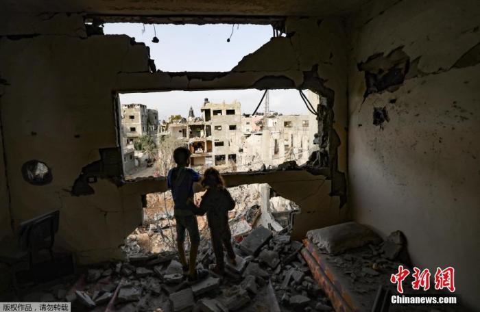 当地时间5月21日,加沙地带,返回家园的孩子看着残垣断壁。