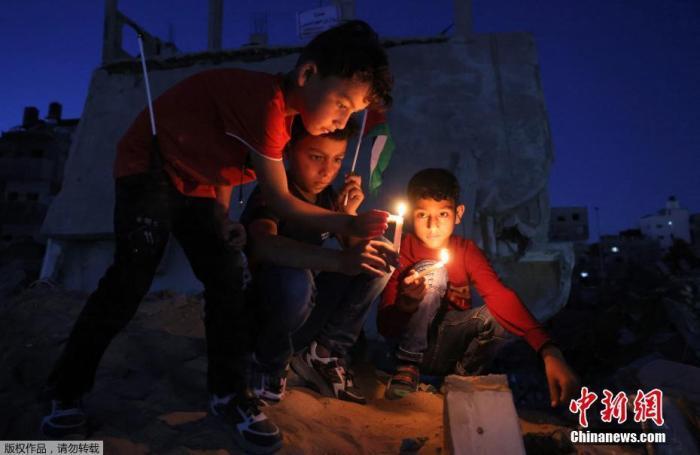 当地时间5月24日,巴勒斯坦儿童在加沙地区被炸毁的房屋废墟上举着蜡烛集会。