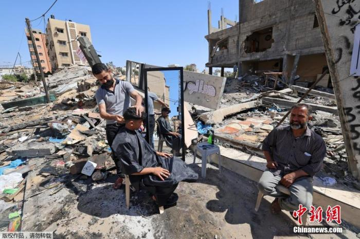 当地时间5月25日,加沙地区,巴勒斯坦理发师Hashim Al-Jarousha在废墟上为民众理发。据悉,他的理发店在巴以冲突中遭以色列空袭被摧毁。