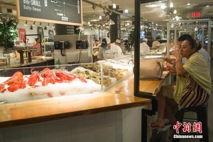 资料图:当地时间5月25日,顾客在美国纽约切尔西市场一家海鲜餐厅用餐。 中新社记者 廖攀 摄