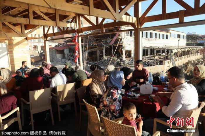 资料图:巴勒斯坦加沙,当地民众在被以色列轰炸而遭到破坏的一处海边咖啡馆中享受休闲时光。 图片来源:Sipaphoto