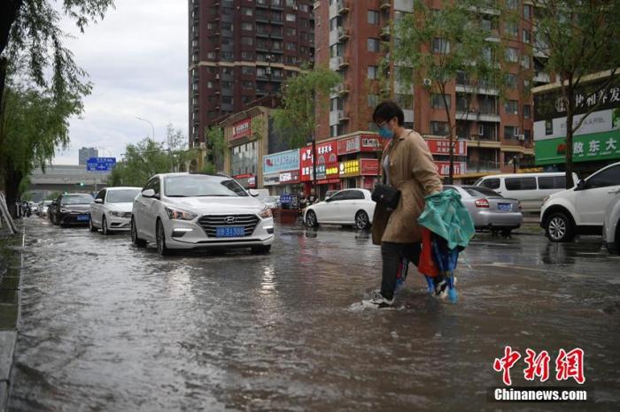 6月2日,吉林省長春市遭遇暴雨,城區多個路段積水成河,多臺車輛被困水中拋錨。當天,吉林省氣象臺發布暴雨、冰雹、雷暴大風、城市內澇風險等天氣預警。圖為市民在積水路段通行。 張瑤 攝