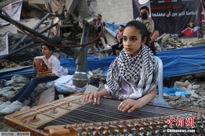 资料图:当地时间6月2日,加沙地带,巴勒斯坦音乐家在遭受以色列空袭的房屋废墟上演奏音乐。