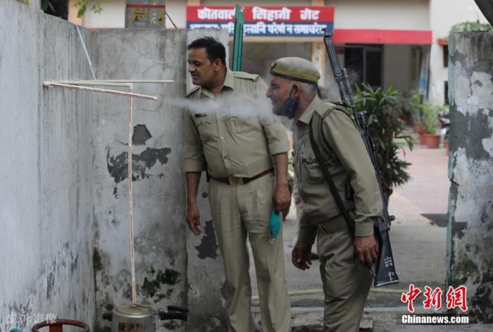 当地时间2021年6月3日,印度北方邦加济阿巴德,印度警察吸入草药蒸汽,作为预防新冠肺炎的措施。 图片来源:ICphoto