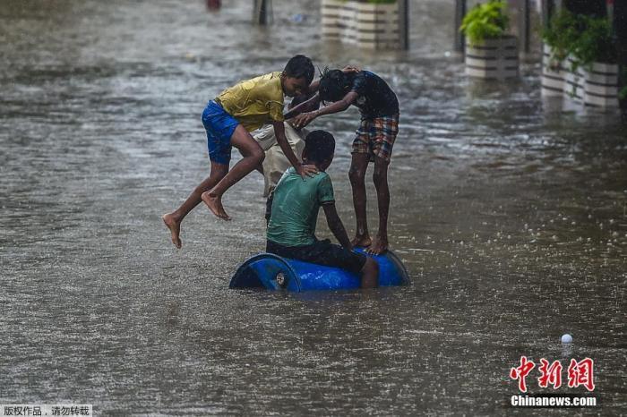 资料图:当地时间6月9日,印度孟买遭遇暴雨天气,街道被积水淹没。图为孩子们在被水淹没的街上玩耍。