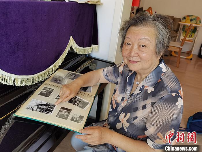 图为6月10日,李筱松展示家庭相册中的老照片。 中新社记者 路梅 摄