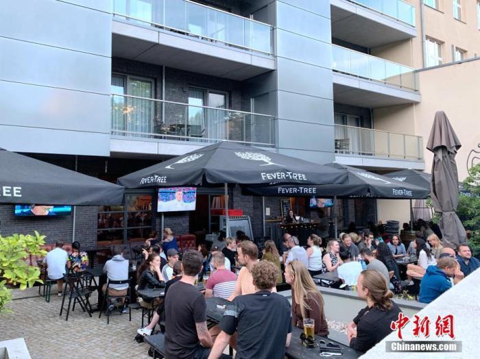 """當地時間6月15日,隨著德國新冠疫情進一步趨穩,多個聯邦州均進一步推進""""解封"""",放松此前采取的防疫措施。柏林市政府當天亦公布了包括放松口罩強制令在內的一系列""""解封""""措施。目前,柏林市內的餐館和酒吧等的戶外座位已不再需要消費者出示新冠檢測陰性報告。圖為柏林一家酒吧露天觀看歐洲杯的球迷。 <a target='_blank' href='http://www.doornamics.com/'>中新社</a>記者 彭大偉 攝"""