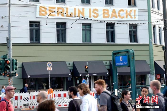 """當地時間6月15日,隨着德國新冠疫情進一步趨穩,多個聯邦州均進一步推進""""解封"""",放鬆此前採取的防疫措施。柏林市政府當天亦公佈了包括放鬆口罩強制令在內的一系列""""解封""""措施。目前,柏林市內的餐館和酒吧等的戶外座位已不再需要消費者出示新冠檢測陰性報告。圖爲柏林一家青年旅社打出""""柏林回來了!""""的標語。 中新社記者 彭大偉 攝"""