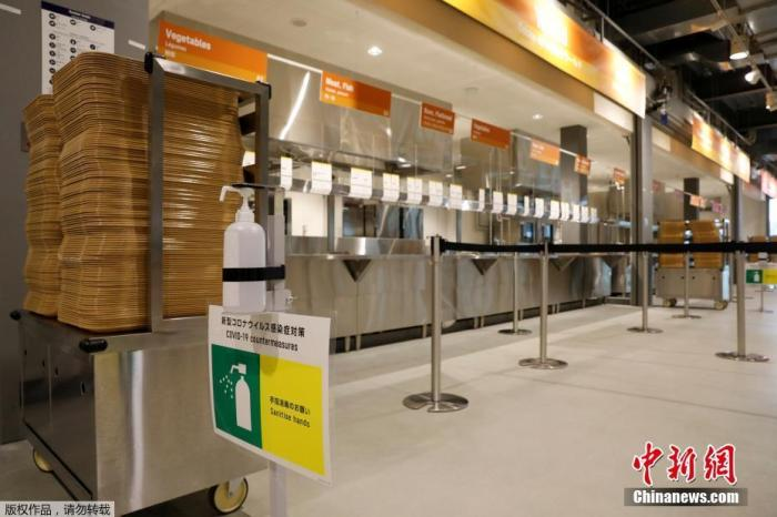 当地时间6月20日,距东京奥运会开幕还有33天时,奥运村首次对媒体开放。图为奥运村餐厅里摆放的洗手液和防疫标识。