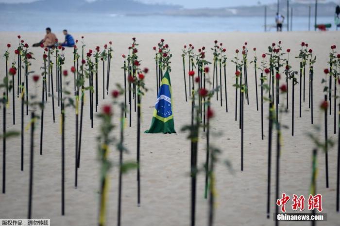 当地时间6月20日,巴西里约热内卢科帕卡巴纳海滩上摆放着玫瑰花,悼念巴西超50万的新冠逝者。图为海滩上的玫瑰与巴西国旗。