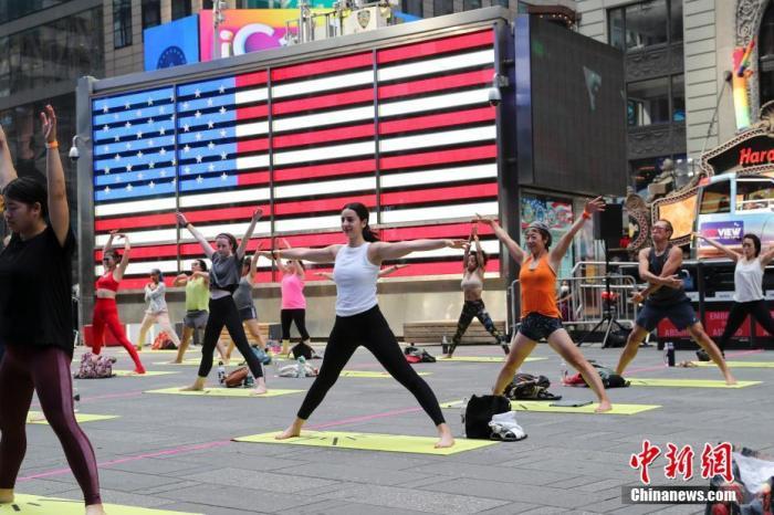 当地时间6月20日,民众在美国纽约时报广场练习瑜伽迎接夏至到来。当日,上千人参加瑜伽练习课程,这项时报广场每年举办的活动去年因疫情停办,今年的活动则加大了每位参与者的空间间隔。 <a target='_blank' href='http://www.chinanews.com/'>中新社</a>记者 廖攀 摄