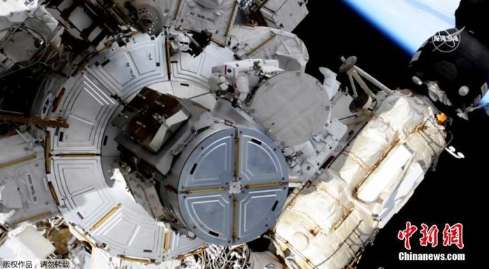 当地时间6月20日,美联社发布国际空间站宇航员执行太空行走任务的视频截图。图片显示国际空间站的两位宇航员进行太空行走并安装太阳能电池板。