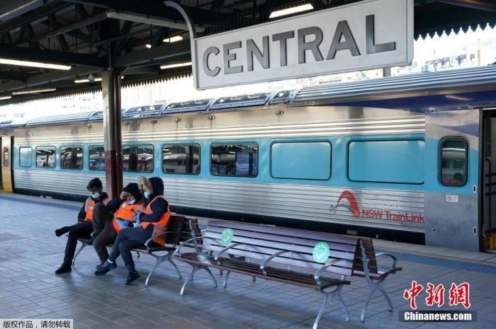��地�r�g6月26日,澳大利���|悉尼,中央�站�瘸丝吞彀∠∩伲�工※作人�T坐在�L椅上。