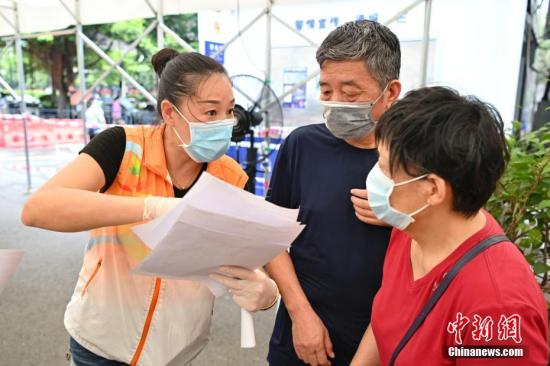 A staff member of No. 2 People's Hospital of Guangdong Province explains to an eldly woman about the COVID-19 vaccination in Guangzhou, Guangdong Province, July 1, 2021. (Photo/China News Service)