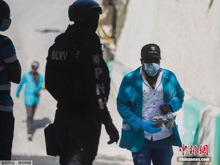 图为法医调查员带走一袋从海地总统住所收集到的弹壳。