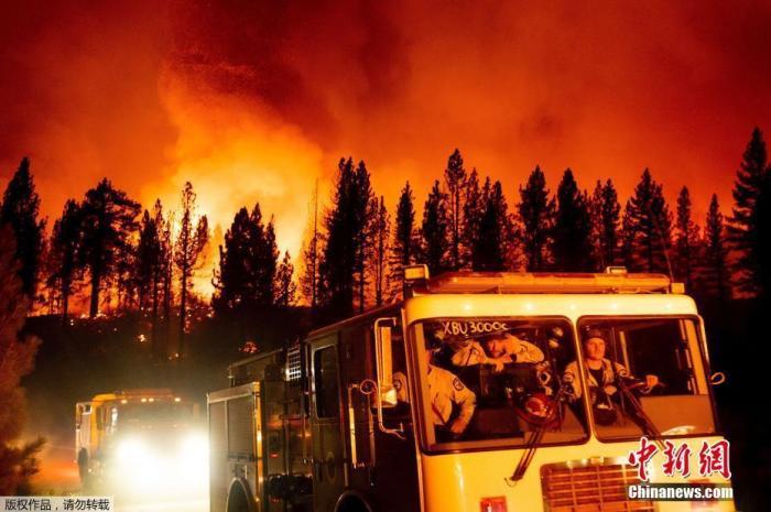 """当地时间7月8日,美国加州,贝克沃斯综合火灾一部分的""""糖火""""在普卢马斯国家森林蔓延,火光映红天空。图为消防抵达现场。"""