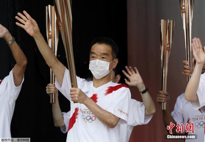 当地时间7月9日,东京奥运会圣火抵达日本东京都,圣火迎接仪式在驹泽奥林匹克公园体育场举行。图为火炬手们挥手致意。