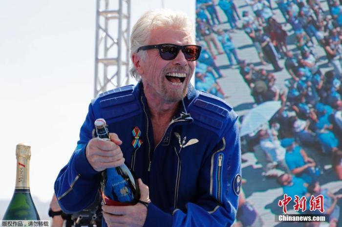 维珍银河公司创始人理查德・布兰森返回地球后开香槟庆祝。