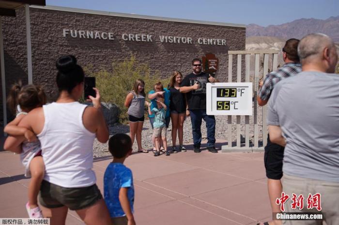 当地时间2021年7月11日,美国加州迎来高温天气,加州死亡谷国家公园迎来高温,民众与温度指示器合影。