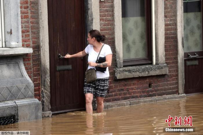 当地时间7月15日,比利时霍格努尔市,一名女士站在家门口被洪水淹没的道路上。