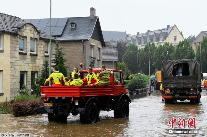 当地时间7月15日,在荷兰法肯堡发生大雨后,救生员乘坐救援车辆路过被洪水冲刷的道路。