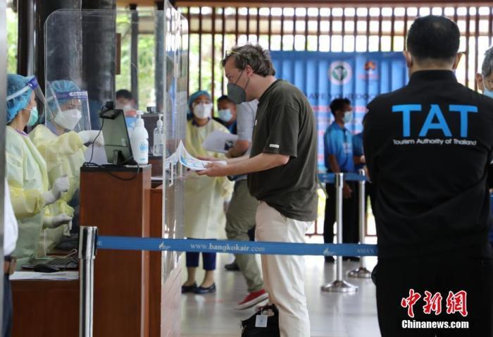 """当地时间7月15日,一名游客在泰国苏梅岛机场办理入境手续。当天,泰国启动""""苏梅岛+""""重新对外开放计划,首批5名国际游客当天搭机抵达苏梅岛。""""苏梅岛+""""包括开放苏梅岛及其附近的帕岸岛、龟岛(涛岛),这3座岛屿均为泰南素叻他尼府境内的著名旅游胜地。 <a target='_blank' href='http://www.chinanews.com/'>中新社</a>发 赵婧楠 摄"""