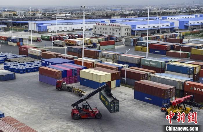 图为7月14日,中欧班列(乌鲁木齐)集结中心旁的货场内,大型机械正在吊运集装箱。 中新社记者 刘新 摄