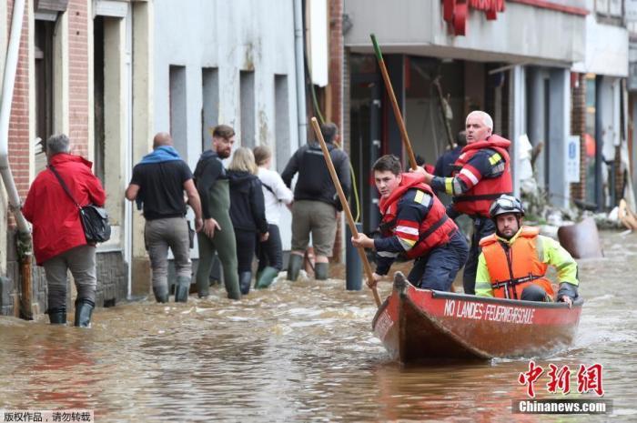 当地时间7月16日,比利时Pepinster,救援队队员撑船穿过受洪水侵袭的地区。