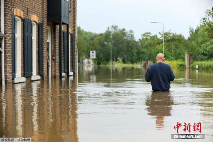 当地时间7月16日,荷兰Guelle,居民在洪水中涉水前进。